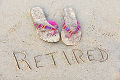 Retirement flip-flops in sand Royalty Free Stock Images