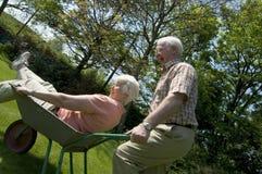 Retirement fun. Retired couple having fun in the garden royalty free stock image