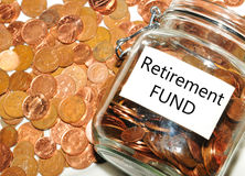 Retirement fund. Retirement concept with jar of money against coins background Stock Images