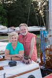 Retirement is Good. Portrait of a happy retired couple on their classic ketch as the late summer sun sets behind a grove of trees Stock Photos