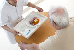 RETIREMENT HOME CARE GIVER. Senior wman eats lunch at retirement home (care, home, elderly Royalty Free Stock Images