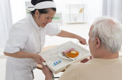 RETIREMENT HOME CARE GIVER. Senior wman eats lunch at retirement home (care, home, elderly Stock Photo