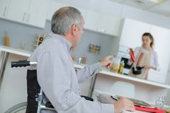 Retirement home with elder man on wheelchair. Retirement home with elder men on a wheelchair Stock Image