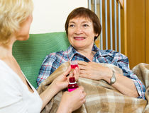 Retirement home employee offering  mixture to aged patient Stock Image