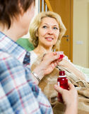 Retirement home employee offering  mixture to  patient Royalty Free Stock Image