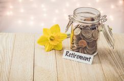 Retirement money jar savings motivational concept on wooden board. Money jar savings motivational concept on wooden board with yellow daffodil flower with soft royalty free stock images