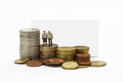 Retirement pay. Figurine from senior couple with eruo coins on white background Royalty Free Stock Image