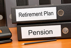Retirement and Pension plan. Text 'Retirement Plan' in black text on a white label of a  black binder and 'Pension' on another binder, both placed on a wooden Royalty Free Stock Images