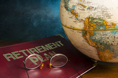 Retirement and Pension planning. Retirement plan book with world globe Stock Photography