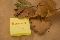 Retirement Plan. Autumn leaves and text with hand writing on wooden table Stock Photo