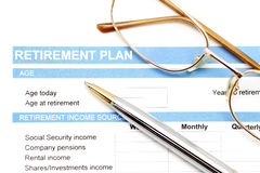 Retirement plan document with pen and glasses Stock Image