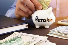 Retirement plan. Man is putting dollar banknote in a piggy bank with sign pension. Royalty Free Stock Photography