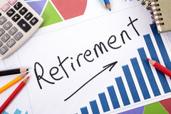 Retirement planning, pension fund growth. The word Retirement written on a bar graph surrounded by pencils, books and calculator Stock Photo
