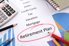 Retirement plan pension fund planning. The words Retirement Plan circled in red with a list of saving and debt obligations surrounded by graphs, charts, books Royalty Free Stock Image