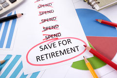 Retirement saving plan, to do list. The words Save For Retirement circled in red with a list of spending obligations surrounded by graphs, charts, books and Royalty Free Stock Images