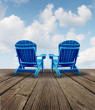 Retirement Relaxation. And financial planning symbol with two empty blue adirondack chairs on a wood patio deck with a sky view as a business freedom concept of Stock Photo