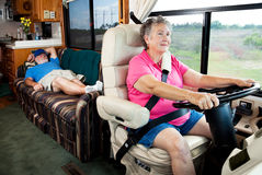 Retirement Road Trip. Senior woman driving the motor home on vacation while her husband sleeps in the back Stock Images