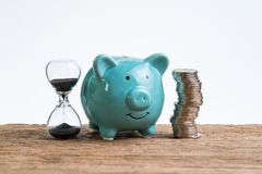 Retirement saving money piggy bank as long term investment concept with stack of coins and sandglass or hourglass on wood table