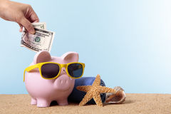 Retirement saving, pension plan, vacation travel planning concept, piggybank. Saving for beach vacation or retirement, with pink piggy bank and sunglasses Stock Images