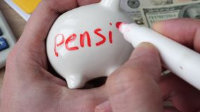 Retirement and savings concept. Man draws a word pension on a piggy bank stock video footage