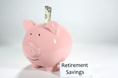 Retirement Savings Pink Piggy Bank. One dollar sticks partly in a pink piggy bank with a label stating retirement savings Stock Image