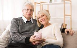 Retirement savings. Senior couple holding piggybank at home