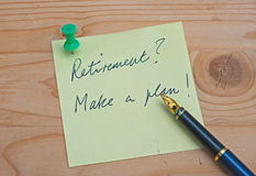 Retirement ?. Text in handwritten script Retirement ? Make a plan! on yellow a post-it note with gold nib pen alongside, background of wooden table royalty free stock photography