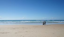 Retirement for Two. Man and wife walking down the beach returning from fishing Stock Photography