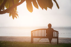 Retirement Vacation Concept. women retired sitting alone on chair that have the sea background. stock photo