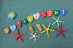 Retirement word with multicolored heart stones. Over green sand with starfishes Stock Photo