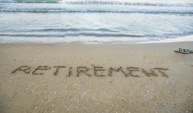 Retirement written on sand by sea at beach. royalty free stock photos