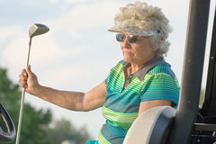 Retired Golfer. A senior female golfer relaxing while waiting in a golf cart Stock Image