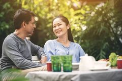Retiro precioso asiático de los pares que tiene una felicidad que habla durante cena en patio trasero Familia feliz después del r imagenes de archivo