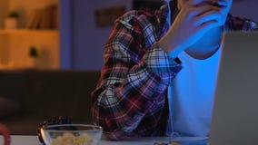 Retlig skolapojke som håller ögonen på online-konkurrens på bärbara datorn på natten, böjelse lager videofilmer
