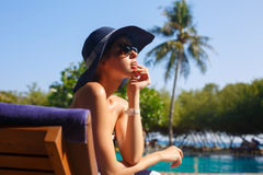 Retouched prtrait of young women in straw hat and stylish beach enjoying the tropical sun and sitting on a deck chair. Young woman in straw hat and stylish beach Stock Images