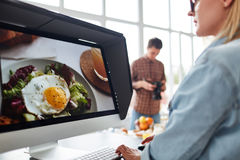 Retouching Food Photography. Professional food designer retouching photo while sitting in front of modern computer, spacious production studio with panoramic royalty free stock image