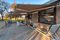 Retractable Awning. Cozy sideyard and deck with a tractable awning stock image