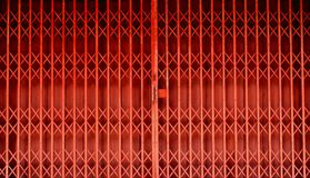 Retractable folding red door gate. Retractable folding metallic red grill in front of a shop Royalty Free Stock Photography