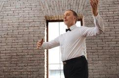 Retraité avec du charme assidu apprenant la valse dans le studio de danse Images libres de droits