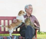 Retraité avec ses animaux familiers Photo stock