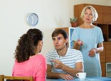 Retraité féminin bouleversé observant les enfants adultes se disputer à la maison Photo libre de droits