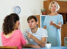 Retraité féminin bouleversé observant les enfants adultes se disputer à la maison Image libre de droits
