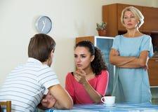 Retraité féminin bouleversé observant les enfants adultes se disputer à la maison Images libres de droits