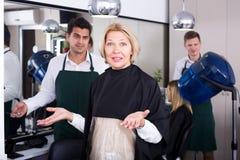 Retraité féminin frustrant ayant le combat avec le coiffeur Images stock