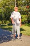 Retraité masculin appréciant la promenade en parc avec le bâton photo libre de droits