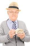 Retraité masculin comptant l'argent Photographie stock