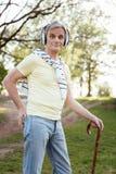 Retraité positif appréciant la musique en parc Photo stock