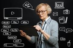 Retraité sérieux indiquant l'écran d'un comprimé tout en communiquant en ligne Image stock