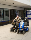 Retraité s'asseyant sur un scooter de mobilité Images stock