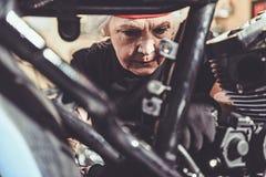 Retraité Undistracted réparant la moto dans la boutique de mécanicien Photo stock